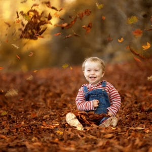 Location portrait photography of child in autumn leaves