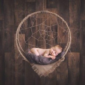 Photograph of newborn baby in dreamcatcher