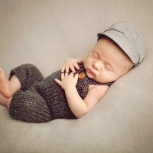 Cute newborn baby in woollen dungarees and engineer's cap