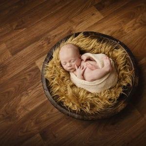 Newborn baby photographed on wooden floor